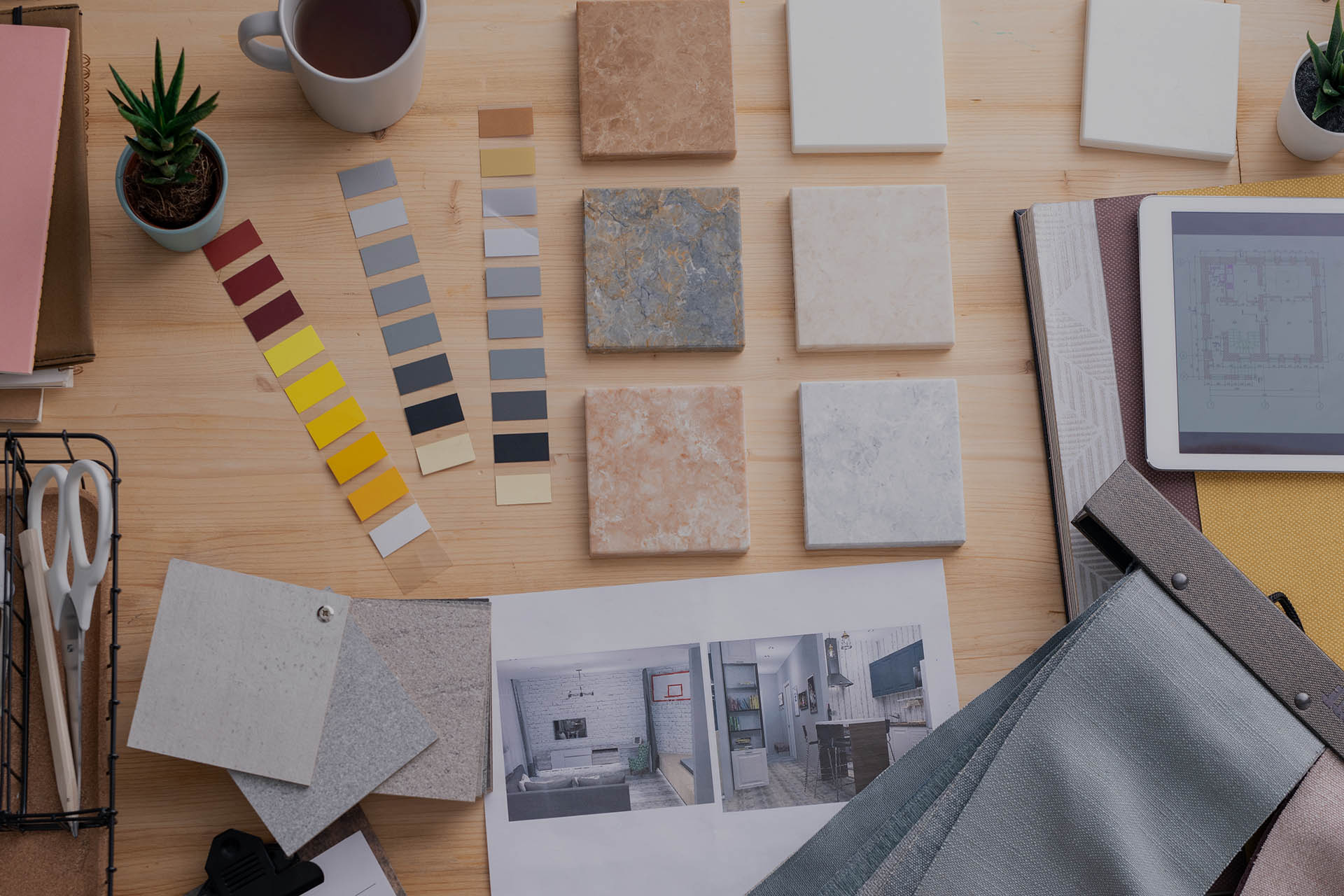 Flat lay of hands of contemporary creative interior designer over workplace during work over new apartment or room in house